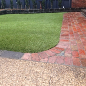 Brick paving, grass, bluestone, pebble path